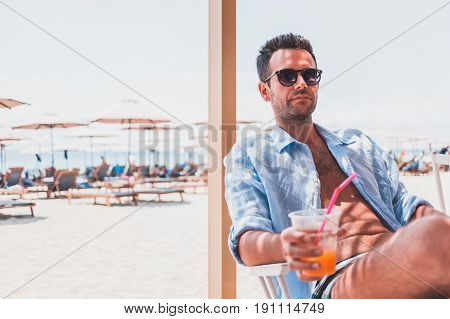 Young man drinking fresh orange juice in the beach bar