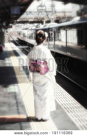 Retro style depiction of a young Geisha on a train station platform in Japan. Faded, nostalgic style image with the obi toned in bright purple.