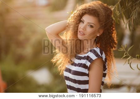 Beautiful young brunette woman with long curly hair,dressed in a white slip dress with dark blue stripes,a nice smile and a sexy mole on left side of lips,big black eyelashes and light make-up,posing in summer in the fresh air among the greenery