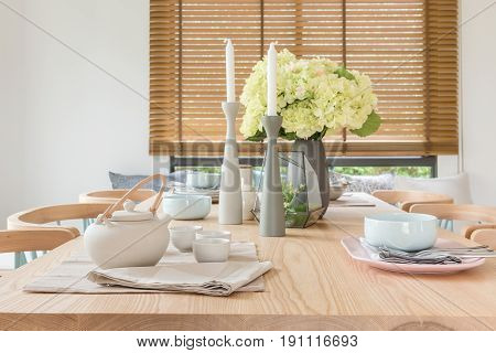 Wooden Dining Table In Modern Dining Room With Table Set And Vase Of Plants