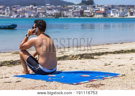 A guy on the phone while enjoying the beach