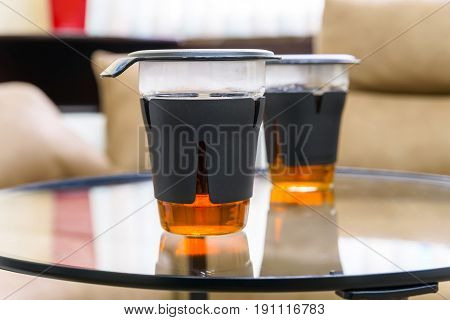 Close up pair of modern glasses full of tea on table