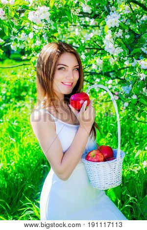 beautiful young woman with the basket full of apples