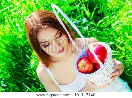 beautiful young woman with basket full of  the apples   in summer time