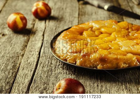 Tarte tatin upside down peach tart on vintage rustic wooden table. Summer baking. French cuisine. Selective focus. Toned image