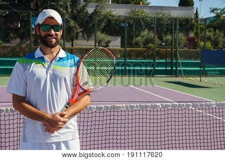 Tennis teacher welcomes you to the tennis court. He is a tennis professional and teaches tennis students in the court.