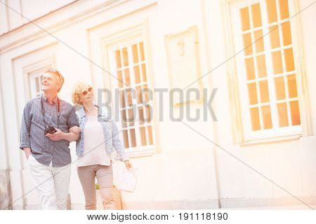 Happy middle-aged tourist couple walking arm in arm by building