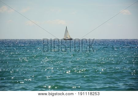 Lonely white sailboat in the blue sea on the horizon, shine and radiance of water