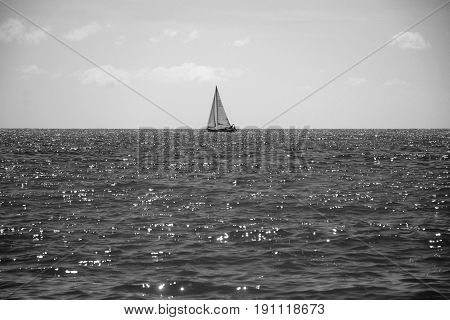 Lonely white sailboat in the blue sea on the horizon in grey color, shine and radiance of water
