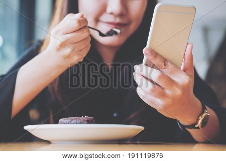 An Asian woman holding and using smart phone while eating brownie on wooden table in cafe