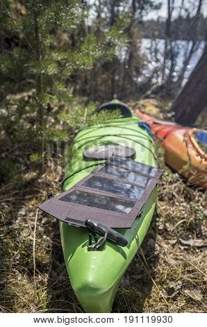 Portable solar panels lie on a green kayak in the forest and accumulate energy.