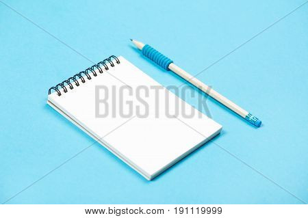 Spiral notepad with pencil as mockup for your design. Note book on pastel blue background.