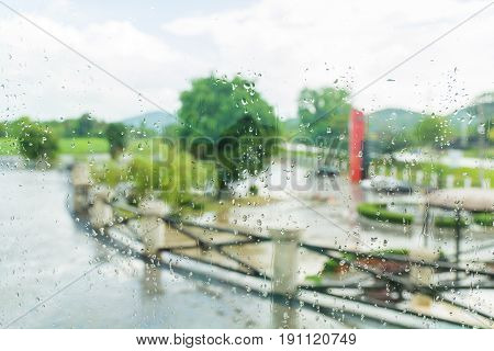 Raindrop on Transparent Glass in Rainy Season with Blur Background of Tree and Fence outdoor Scene