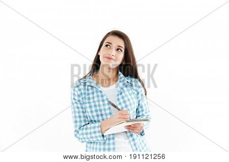 Portrait of a pensive pretty woman making notes in notepad and looking away at copy space isolated over white background