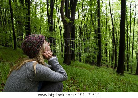 horizontal side view portrait of Caucasian young woman with long blonde hair and colorful wool hat leaning meditating with eyes closed in a green forest