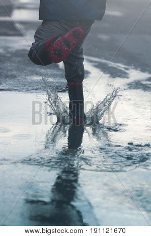 vertical rear view of kid jumping and splashing with water in puddles after rain