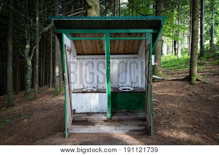 horizontal front view of outdoor toilet booth latrine made of wood planks with two seats in the forest