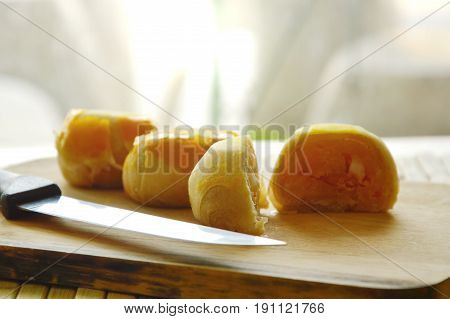 Chinese pastry stuffed mashed bean and salty egg yolk on wooden chop block