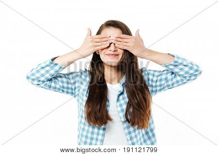 Young brunette funny girl grimacing at camera and hiding face with hands isolated over white