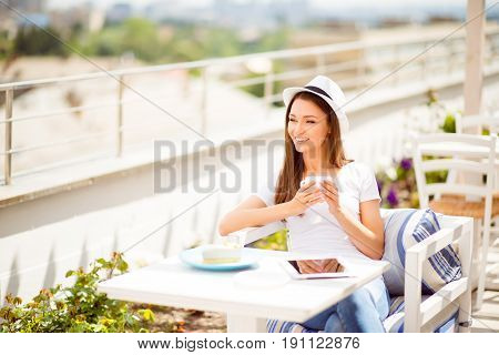 Enjoying Coffee At The Summer Vacation On A Roof Top Open Air Light Restaurant. Young Lady Is So Dre