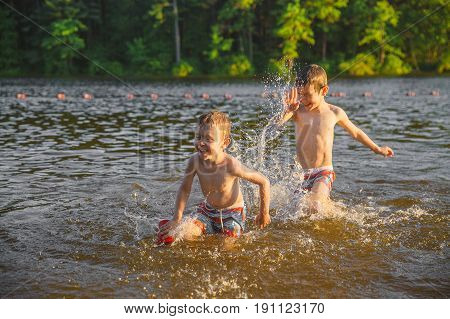 Laughing children splashing in the lake. Two boys having fun and playing in water outdoors. Summer vacation concept