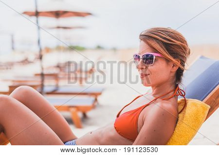 Young beautiful woman sunbathing on the beach
