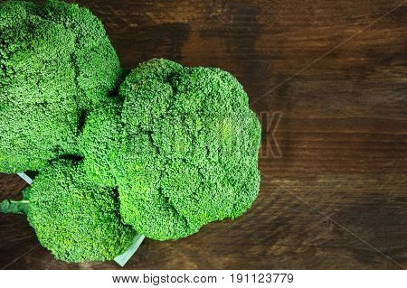 A photo of broccoli heads in a crate, shot from above on a dark rustic texture with a place for text