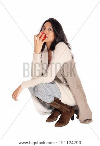 A beautiful Hispanic woman eating a red apple crouching on the floor isolated for white background.