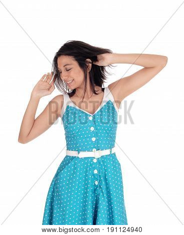 A smiling gorgeous young woman standing waist up in a blue dress with hands on her head smiling isolated for white background.
