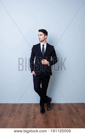 Full Size Portrait Of Stylish Young Brunete Banker Standing On Gray Background. He Looks Stunning! I