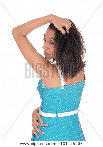 A serious young woman standing waist up in a blue dress from the back with one hand on her head isolated for white background.