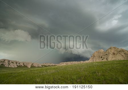 A shelf cloud accompanies this thunderstorm as it approaches a rocky hillside in the Great Plains.