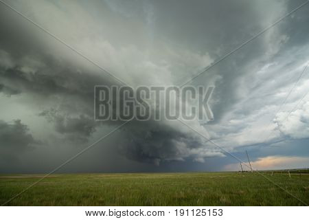 An arcing shelf cloud races forward as a severe thunderstorm approaches.