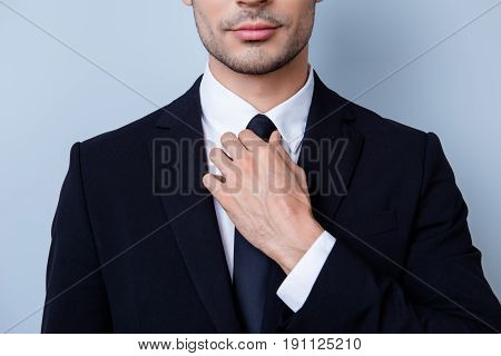Close Up Cropped Portrait Of Young Handsome Businessman Lawyer In Suit. He Is Fixing His Tie. He Sta