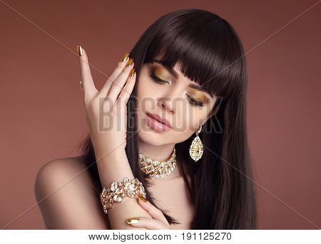 Nails manicure. Beauty girl brunette portrait. Fashion golden jewelry women set. Sexy female with healthy brown hair style isolated on studio background.