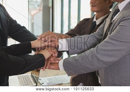 young asian businessman joining united hand business team touching hands together after complete a deal in meeting - unity harmony teamwork partnership collaboration corporate concept.