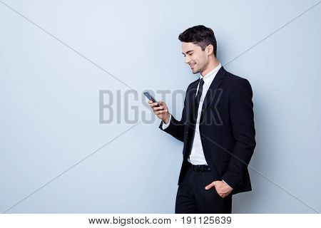 Young Cheerful Brunete Lawyer Is Standing On The Pure Light Blue Background And Smiling, Reading Goo