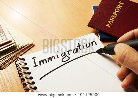 Hand is writing Immigration on a note.
