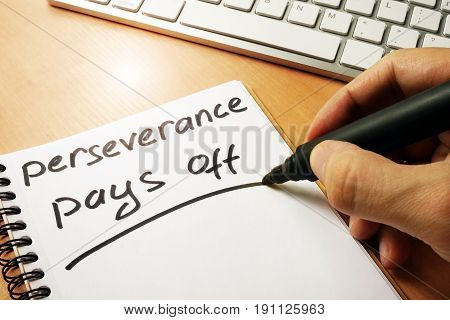 Hand is writing perseverance pays off on a note.