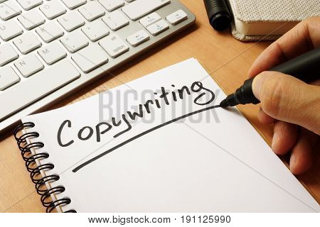 Hand is writing Copywriting on a note.