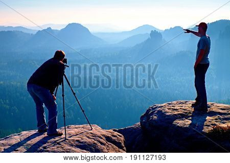 Hiker and photo enthusiast stay with tripod on cliff and thinking. Dreamy fogy landscape blue misty sunrise in a beautiful valley below