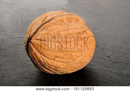 whole brown walnut on a slate board