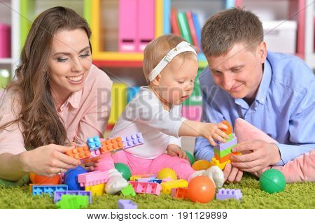 Happy parents playing with adorable little daughter