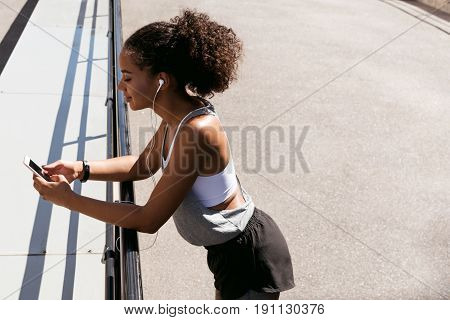 Side view of a woman using cell phone, taking a break during workout
