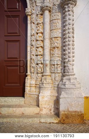 Old church door with Manueline style frame and rich ancient stone carvings artwork