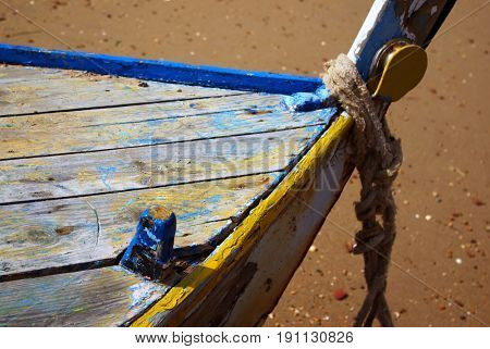 Detail of abandoned fishing boat anchored in the beach