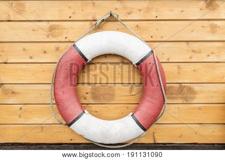 Lifebuoy hanging on a wooden wall. Outdoors