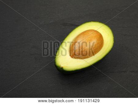 Fresh Ripe Green Avocado On Black Slate Board