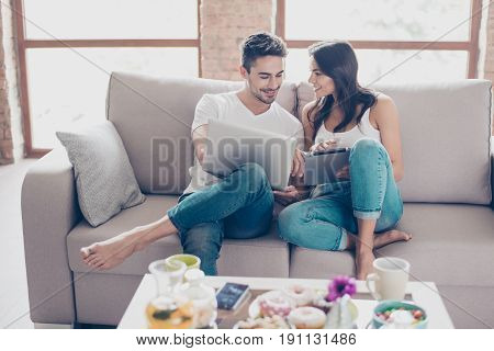 Cheerful Happy Couple Is Doing Online Shopping In Internet At Home Indoors. They Are On Cozy Beige C