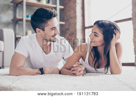 Together Forever. A Couple Of Young Beautiful Lovers Are Lying On The Beige Cozy Carpet Indoors At H